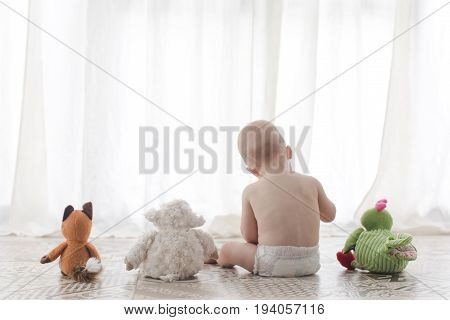 Back view of small boy sitting and playing with soft plush toys.