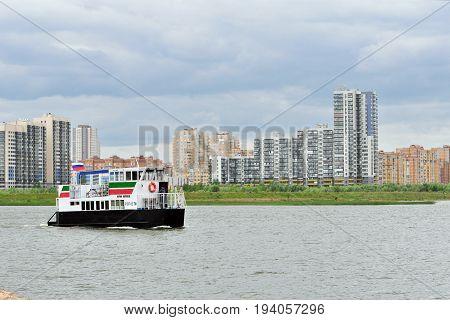 Kazan, Tatarstan, Russia - June 25, 2017. View of Novo Savinovsky district of the city of Kazan, the river Kazanka. River boat (cutter) Yuri Karpeev.