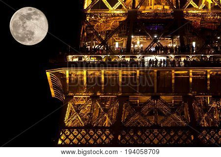 People in a restaurant in Eiffel tower at moonlight