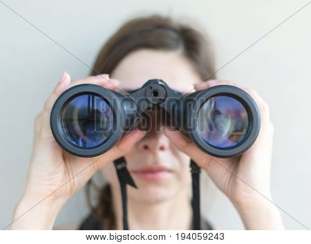 Girl looking through the binoculars. Find and search concept.