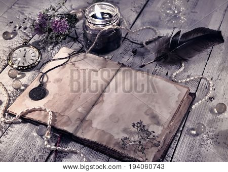 Retro styled still life with old diary, black candle and mystic objects. Vintage romantic concept. Mystic and occult still life