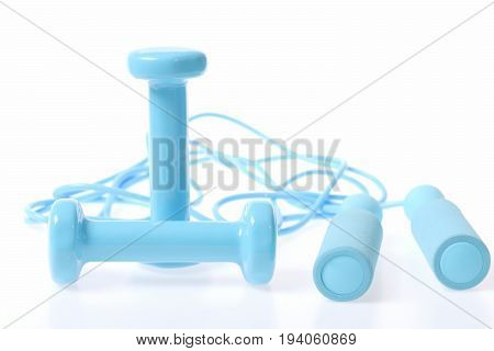 Pair Of Cyan Dumbbells Lying Crosswise Near Rope For Skipping