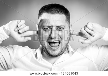 Stressful unpleasant situation conflict. Angry mad young man plug closing ears with fingers protecting from loud noise. Guy not wanting to listen black and white picture