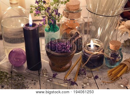 Black candles with glass jars and mystic objects. Alternative medicine, old pharmaceutic and homeopathic concept. Mystic and occult still life, vintage medical background