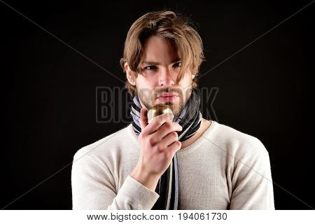 Man with beard and attentive look wears striped scarf and holds golden apple as symbol of ownership. Isolated on black background. Concept of confidence