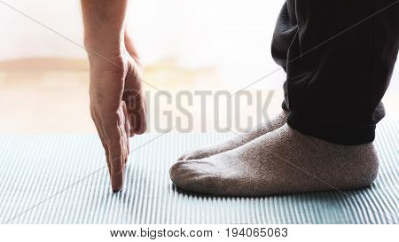 Adult person doing some yoga and meditation exercises on a mat in a class. Empty copy space for Editor's text.