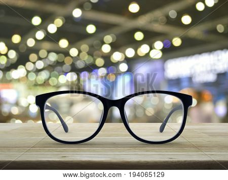 Black eye glasses on wooden table over blur light and shadow of shopping mall Business vision concept