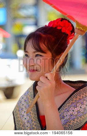 CHIANGMAI THAILAND - JANUARY 25 2015: Indigenous girl with local traditional costume holding local paper umbrella in parade of 22nd Traditional Skirt Fabric and The Indigenous Product and Culture Festival in Mae Chaem Chiangmai Thailand