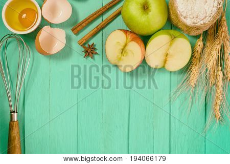Bakery background comprise apple wheat flour egg and cinnamon on blue wood table with copy space.Prepare ingredient for baking apple cake on wood table. Top view bakery background concept. Bakery background with pastel color.