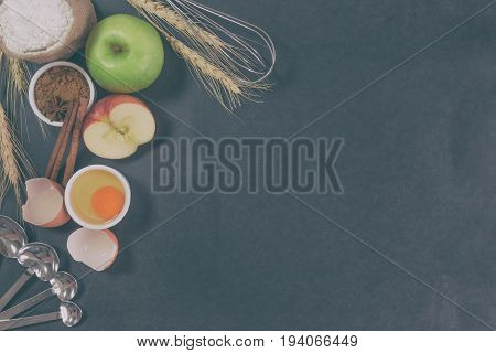 Bakery background comprise with apples wheat flour egg and cinnamon on granite table with copy space.Prepare ingredient for baking apple cake on granite background. Bakery background concept. Bakery background in dark tone style.