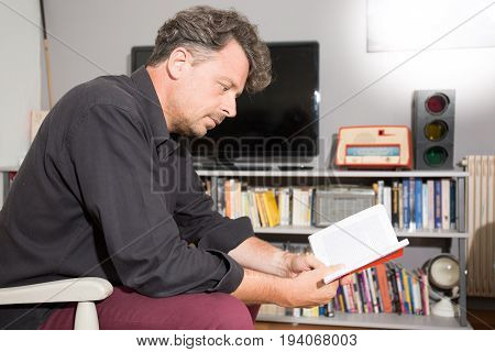 Mature Man Reading Newspaper Sitting In Sofa