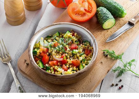 Salad made of couscous with vegetables in a bowl for healthy meal. Cooking of traditional Israeli Ptitim for lunch. Moroccan food and ingredients on a table. Top view.