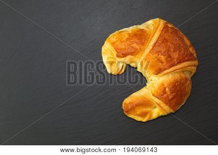 French croissant on black slate stone plate for morning breakfast or break time with copy space