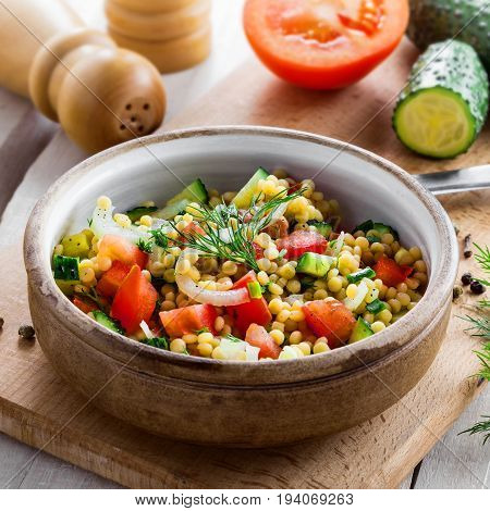 Traditional Israeli healthy meal Ptitim with tomatoes cucumber and onion for delicious healthy breakfast. Cooking of classic Moroccan couscous with vegetables.
