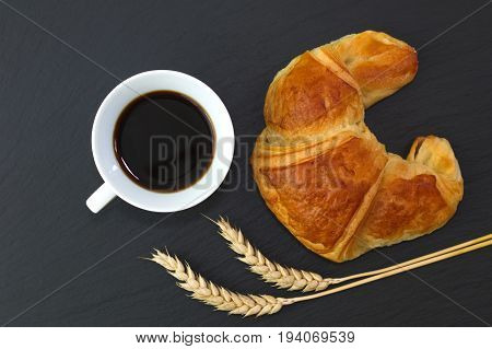 French croissant and coffee on black slate stone plate for morning breakfast or break time with copy space