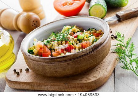 Delicious Israeli couscous Ptitim with vegetables on a white wooden table. Cooking of healthy vegetarian food for the meal. Traditional Moroccan cuisine.