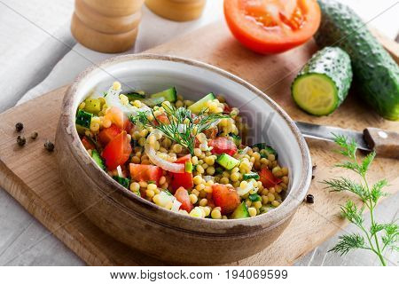 Cooking of couscous with tomatoes cucumber and onion in a bowl for healthy breakfast. Traditional Israeli food Ptitim with vegetables. Moroccan cuisine meal on white wooden table.