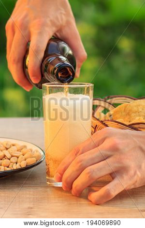 Young man holds bottle of beer and fills glass. Male hand pouring beer into glass on wooden table with potato chips in wicker basket peanuts in plate and bowl. Selective focus on bottle neck