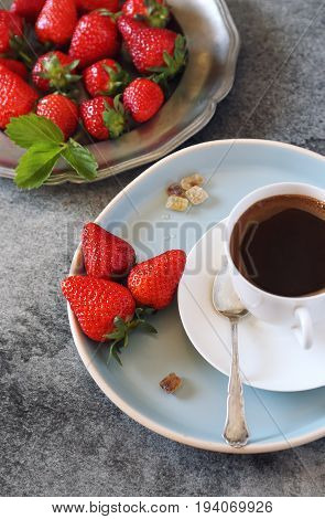 Raw red strawberries and cup of black coffee. Top view