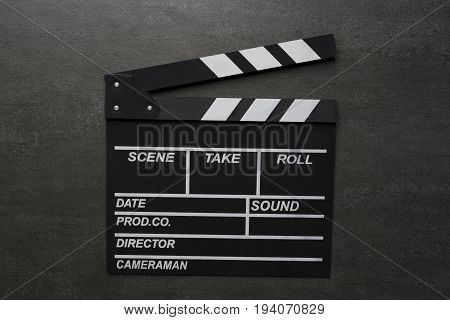 movie clapper on black table top view