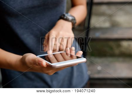Close-up image of young hipster girl using modern smartphone device.