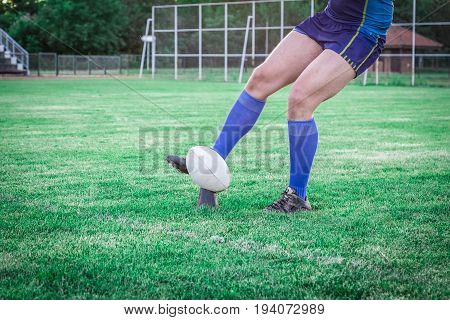 Rugby player kicking the ball for goal at stadium