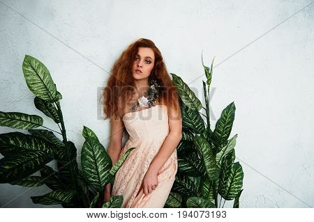 Beautiful red-haired girl on the background of plants with broad green leaves.In lace dress powdery pastel cream color