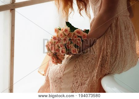Beautiful red-haired girl romantically sitting on the edge of the bathtub and holding a bouquet.The face is not visible on the background of plants with broad green leaves. In lace dress powdery pastel cream color