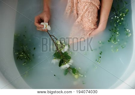 Beautiful romantic red-haired girl sitting in the bath and holding flowers .The face is not visible. In lace dress powdery pastel cream color