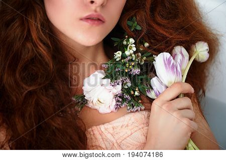 Beautiful romantic red-haired girl sitting in the bath and holding flowers .part of the face is not visible. In lace dress powdery pastel cream color