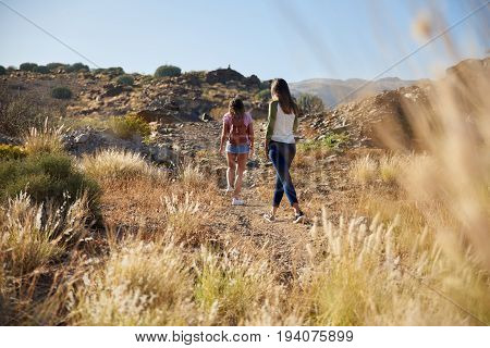 Two Young Girls Strolling Up Hillside