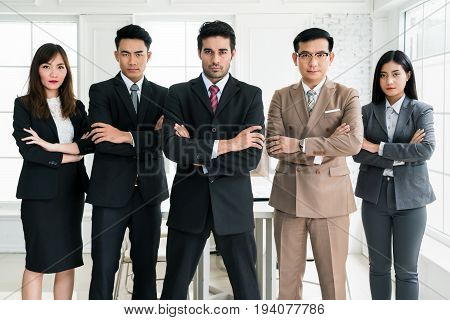 Five confident muti ethnicity business people crossing their arms in front of a bright window. Businessman and businesswoman standing in office.