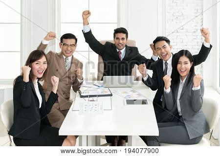 Group of muti ethnicity business people team success achievement with arm raised to celebrating good job in the office. Business people team togetherness happiness Concept.