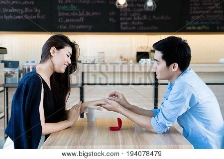 Asian handsome man putting wedding ring on and proposing to his beautiful woman in cafe. Love anniversary surprise people and holidays concept