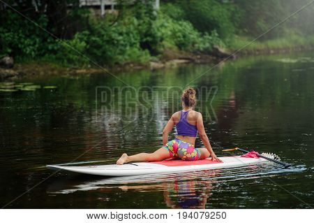 Young Woman Doing Fitness On A Board With An Oar. Side View - The Concept Of Harmony With Nature, A