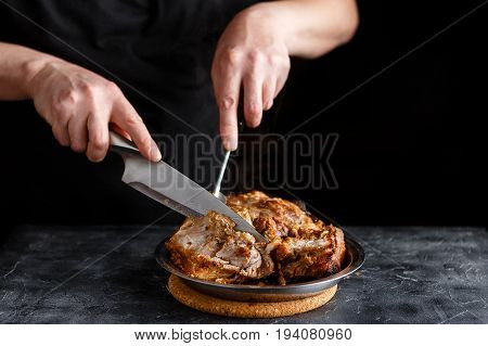 Man cuts roasted pieces of pork shoulder blade in metal plate on dark background