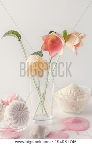Natural ice cream pink and white melts and flows down beautifully. Beautiful and delicate bouquet of flowers made of ice cream on a white background. Cover for the magazine, poster