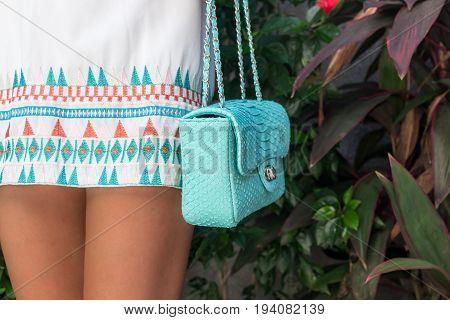 Woman holding luxury snakeskin python handbag. Fashion bag concept on a tropical island.