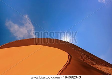 Large Sand Dune in Sossusvlei in the Namib Naukluft National Park, with tiny people at the peak, with the blazing hot sun peeping over the edge.  Namibia, Southern Africa