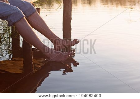 a man sits on a wooden bridge and dip feet in warm water for a lake in the summer