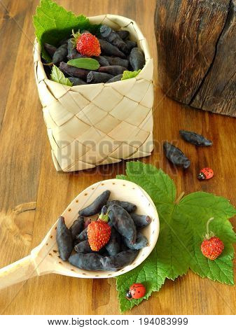 Honeysuckles and strawberries in a wicker basket and a wooden spoon on a wooden background