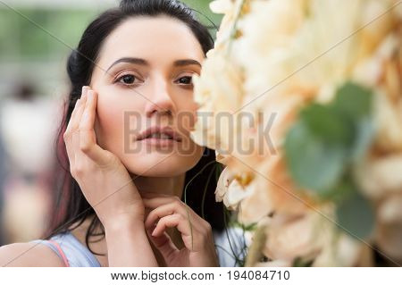 Fashion portrait of woman with flowers. Shallow depth of field