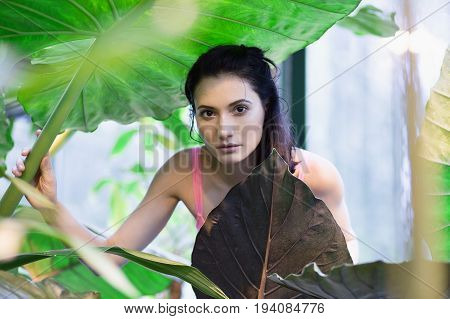 Young beautiful girl in sweamsuit with huge green leaves around