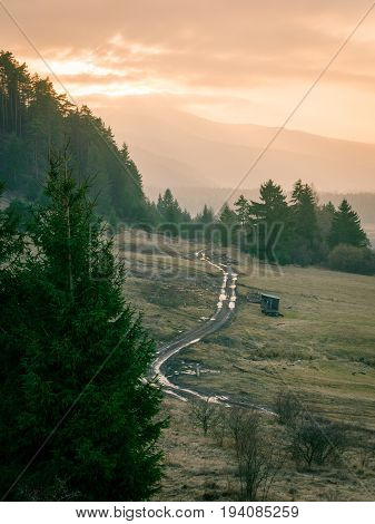 Backcountry dirt road wuth many puddles on foothills of lower tatras mountain in Slovakia at sunset time.