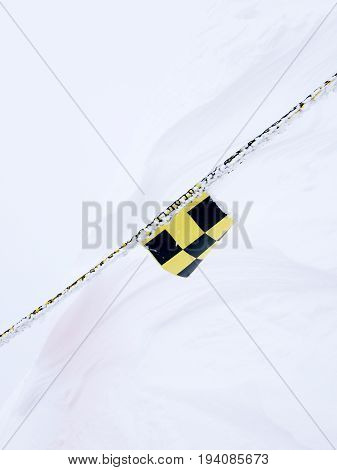 Small avalanche flag hanged on rope at snow background. Warning symbol in the mountains.