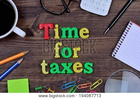 Time for taxes on wooden table closeup