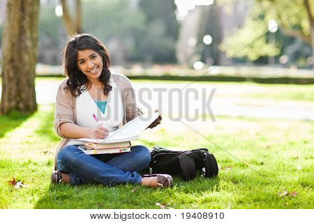 A shot of an asian student studying on campus lawn