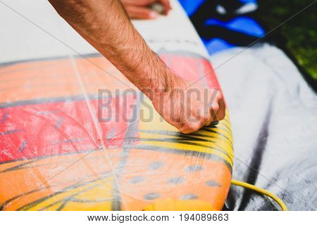 Close up view of hand waxing surf board outdoors. Man is removing or applying wax to surfboard shortboard on vacation. Traces of wax are visable.