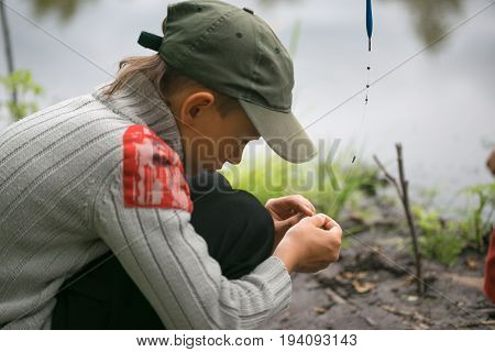 Boy On Fishing Clothes Bait On Hooks Fishing Rods.