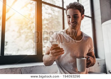 Handsome man on kitchen is smiling drinking coffee in the morning and looking at smart phone.